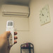 Man's hand holding a remote control to turn on the air conditioner