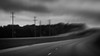 Inclement Weather (Anne Worner) Tags: anneworner bw bend blackandwhite blur car composerpro dark doubleglass headlights impressionistic lensbaby manualfocus manualfocuslens mono moody powerlines powerpole road silverefex wideangle haunting sky clouds