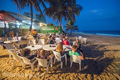 Groups of people are seated at tables along the beach at a restaurant. Monrovia, Liberia (Remsberg Photos) Tags: africa developing liberia monrovia westafrica beach tropical travel tourist food restaurant meal palmtrees beachside tourism gather share engage