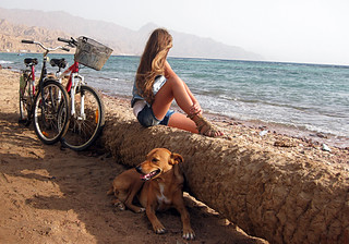 Girl with bicycle near sea