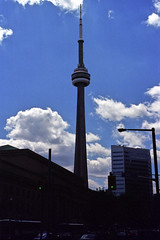The CN Tower Pierces the Sky (pmvarsa) Tags: summer 2000 analog colour film 135 kodak kodakroyalgold400 royalgold 400iso nikonsupercoolscan9000ed nikon coolscan cans2s architecture natural light shadow blue sky cloud contrast building cn tower street skyscraper sun backlight canon ftb canonftb classic camera downtown toronto ontario canada