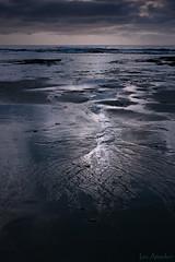Retreating (ian_underthesea) Tags: beach low key moody rocks sand dark