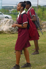 School Gals (Poocher7) Tags: people portrait female schoolgirls uniforms reddresses brownshoesandsocks backpacks headphones music schoolsout students college mobay montegobay jamaica westindies caribbean fence rocks grass jamaicangirls schooluniforms