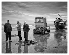 Waiting for the skipper (AEChown (away now)) Tags: fishermen fisherman fishingboat bulldozer beach reflections thestade hastings monochrome mono bandw people boat