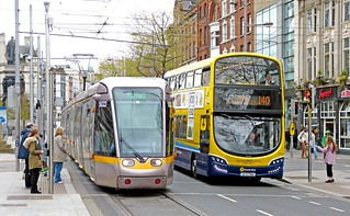 LUAS Dublin: Green Line 5022 northbound pulling away from the traffic lights at the lower end of O'Connell Street alongside Dublin Bus SG69