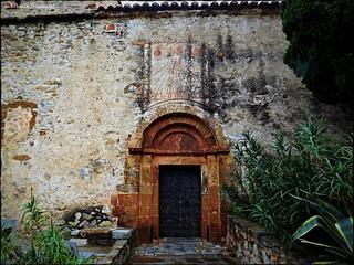 Porte de l'église de Castelnou avec son vieux cadran solaire