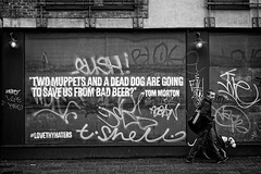 Two Muppets and a Dead Dog (garryknight) Tags: sony a6000 on1photoraw2018 london allrightsreserved themonoseries monochrome blackandwhite 50mmf18 bricklane poster muppet dog man walking street candid