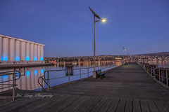 Port Lincoln at dawn (Malcom Lang) Tags: port lincoln bostonbay boston bay foreshore jetty wharf seat fishermen fishingrod fishing rod light lights solar pole poles wood plank bench rail railing star earlymorning early morning grainsilos grain silos town reflection water sea ocean southaustralia southern south southernaustralia southerneyrepeninsula southernocean blue beach sky travel traveling travelaustralia canoneos6d canon canon6d canonef2470mm canonef mal lang photography australia australian aussie