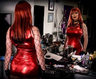 Redhead in shiny red dress: reflection in the mirror