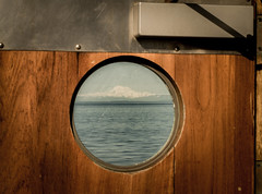 Mt. Baker through the porthole window of the Ferry Coho leaving Victoria, B.C. Canada (Paul T. Marsh/PositivePaul) Tags: 2018 paultmarsh leicad3 leicadigilux3 window fadedcolor april2018 britishcolumbia porthole sea waterways wwwpaulmphotographycom ocean victoriabc color vancouverisland springvacation lightroomcc mtbaker paulmarshphotography canada pacificnorthwest volcano olympus40150mmlens mountain