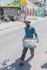 Snack seller, Bali (jeremyhughes) Tags: bali street vendor snacks seller commerce man work sunshine sunny hot road indonesia sony blue hat rx1r rx1rii zeiss 35mm
