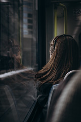 Reflection (Hoss Lake) Tags: girl train street ctrain reflection cold light vintage seat sony ride hair a6300 24mm 35mm crop sidewalk buildings