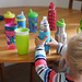 Toddler with braided blonde hair sets stainless steel sippy cup among other sippy cups on kitchen table