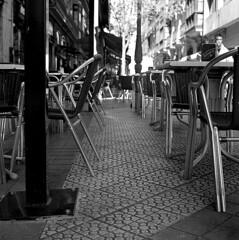 Al fresco (Gabo Barreto) Tags: bilbao paisvasco basquecountry spain chair tables outside pavement restaurant film 120 6x6 mediumformat tlr twinlensreflex kodak trix analoguephotography monochrome blackandwhite selfdeveloped scannedfromfilm shine