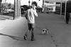On the Phone With a Tiny Dog (bhop) Tags: los angeles california leica m6 leicam leicam6 rangefinder kodak trix bw monochrome film canon 50mm f14 screwmount black blackandwhite dog phone downtown la downtownla city streetphotography street