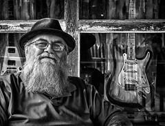 Guitar Man (Anne Worner) Tags: anneworner em5 olympus bw beard candid glasses guitar hat man mono older shirt street streetphotography streetportrait window windowframe blackandwhite