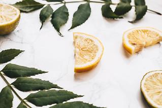 Close up of juicy lemon slice. Lemons and leaves in background
