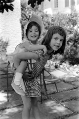 042168 02 (ndpa / s. lundeen, archivist) Tags: nick dewolf nickdewolf photographbynickdewolf 1968 1960s bw monochrome blackwhite blackandwhite 35mm film april neworleans louisiana children kids child girl girls siblings sisters carry carrying nicole vanessa bonnet hat piggyback piggybackride missingatooth lemlehouse lemlehome