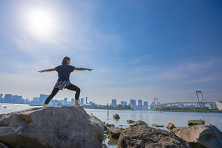 Young woman practicing yoga on rock, in capital city