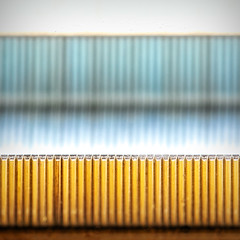 the great half-inch chasm (MyArtistSoul) Tags: metal steel sharp staples swingline sf4 parallel lines wood table yellow reflection blue right angles macro minimal abstract geometric bilateral symmetry imperfect broken pattern square 5099