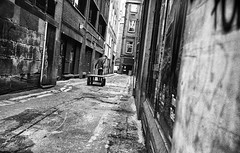 PHOTINGO Challenge - Pulling (Mister G.C.) Tags: street urban photography blackandwhite bw leica leicamini leicaminiii elmar f35 primelens fullframe compactcamera compact camera autofocus autofocusing streetphotography urbanphotography shot image photograph candid people worker man male guy alley alleyway sidestreet pulling cart barrow gritty photingo challenge monochrome town city analog analogphotography analogue 35mm film filmcamera schwarzweiss strassenfotografie mistergc glasgow scotland europe