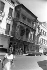 0403b68 30 (ndpa / s. lundeen, archivist) Tags: nick dewolf nickdewolf photographbynickdewolf april 1968 1960s bw blackwhite 35mm film monochrome blackandwhite neworleans louisiana nola candid city citylife streetlife streetphotography frenchquarter building buildings architecture business sign felixs felixsbar bar restaurant balcony balconies ironwork fireescape street car vehicle automobile parkedcar people pedestrians woman glasses sunglasses shades purse handbag barrels signs truck ibervillestreet 739ibervillestreet