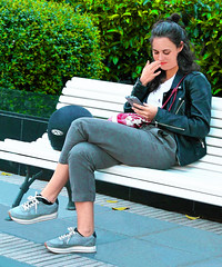 Smiling while reading a message (chrisk8800) Tags: youngwoman girl cellphone message smiling bench sneakers bushes barcelona