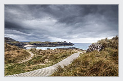 Clachtoll with Split Rock in the background (Katybun of Beverley) Tags: splitrock clachtoll assynt sutherland scotland westhighlands northwesthighlands beach boardwalk grasses rock moodyclouds moodysky moody mood landscape seascape shoreline shore sand outdoors scenery scenic