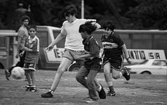 a todo futbol (ojoadicto) Tags: futbol plaza calle chicos blackandwhite blancoynegro reflex callejera cotidiano varones muchchos young children playing