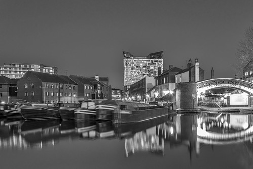The cube behind brick buildings alongside a water channel in the central Birmingham, England