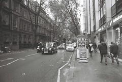 London (goodfella2459) Tags: nikon f4 af nikkor 24mm f28d lens ilford delta 400 35mm blackandwhite film analog city streets london taxi cabs buildings treets road pedestrians people bwfp