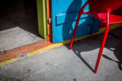 Red chair, blue door [Explored] (Franck_Michel) Tags: floor door chair red blue concrete vivid sun shadow highcontrast entrance restaurant