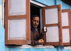 Through The Window (gooey_lewy) Tags: indian india gent bloke man male protrait window shop keeper road side hill cart tea bazaar cup shutters