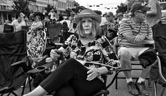 Interrupted Conversation (Anne Worner) Tags: redpoppy2018 anneworner georgetown georgetownpoppyfestival2018 ricohgr silverefex texas bw blackandwhite candid chairs cupholder hat man mono people phone shoes shorts strawhat street streetphotography watch woman stadiumchairs