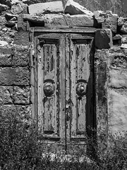 Locked door (kurjuz) Tags: malta rabanemel rabat abandonedroom blackandwhite door doorhandles lock peelingpaint ruins stone