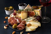 Glass of red wine and cheese plate with pieces moldy cheese, prosciutto, pickled plums, olives, grapes, figs, honey, pear, nuts on black slate (alena.alekseeva.rudenko) Tags: prosutto prosciutto bekon glass wineglass wine italian drycured ham cheese plate background moldy piece styling block pickled plums grape bunch olives figs pear honey gourmet food dried almonds cashews nuts composition style gray ingredient board dairy various types view top wood group cut organic snack meal delicious product appetizer delicatessen life still