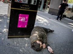 A Sign of the Times (Leanne Boulton) Tags: urban street candid portrait streetphotography candidstreetphotography sociallandscape socialdocumentary streetlife man male sleeping lying trash waste bin juxtaposition sign flickrfriday streetportrait homeless beggar vagrant powerful sad sadness reality gritty grime poignant documentary journalism reportage hipshot dutchangle pink tone texture detail depthoffield bokeh naturallight outdoor light shade shadow city scene human life living humanity society culture people lifestyle tragedy canon canon5d 5dmkiii 24mm wideangle ef2470mmf28liiusm color colour glasgow scotland uk