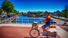 Postbode (Travis Daki) Tags: post man woman bike cycling lake canal bridge summer sun tree street outdoors