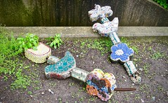 Down (Crawford Brian) Tags: sculpture broken concrete mosaic tile rust flowers fallen down dirt grass weeds