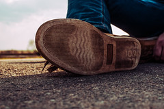 A guy is sitting on a longboard resting. Shoes have worn off from riding on the longboard. Need new shoes for sports (ivan_volchek) Tags: shoe footwear wood wear old dark closeup people fashion style stylish wooden sport fit nature brown isolated white hand healthy