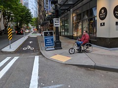 A wheelchair modified for use with hand crank (Seattle Department of Transportation) Tags: seattle sdot transportation donghochang wheelchair modified hand crank crosswalk curb ramp bike lane downtown pbl sign