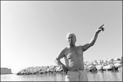 (Directions) (Robbie McIntosh) Tags: leicam9p leica m9p rangefinder streetphotography 35mm leicam blackandwhite bw biancoenero bn monochrome autaut candid strangers leicaelmarit28mmf28iii elmarit28mmf28iii elmarit 28mm seaside rocks colonnaspezzata man belly fat boxer tan
