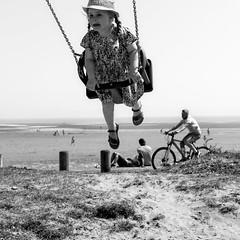 Girl on a Swing (stevedexteruk) Tags: blackpill mumbles swansea sea swing child cycle bicycle 2018 wales bw mono monochrome blackandwhite park square squareformat 1x1