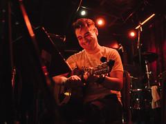 Gabriel (BurlapZack) Tags: olympusomdem5markii panasonicleicadgsummilux25mmf14 vscofilm pack01 dentontx danssilverleaf keepdentonthrashing nickthrasher livemusic localmusic memorial inmemoriam availablelight lowlight highiso smile musician guitar guitarist acoustic stage venue bar red laugh tribute