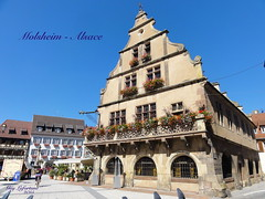 MOLSHEIM, ALSACE en FRANCE, Le METZIG MONUMENT HISTIRIQUE (Guy Lafortune) Tags: bâtiment monument historique fenêtres balcon fleurs place centre vélo personnes hôtel maison rue route road street historic building windows square house people bicycle hotel center flowers balcony blue sky ciel bleu sunny plante plant lamp lampe lampadaire france beautiful weather