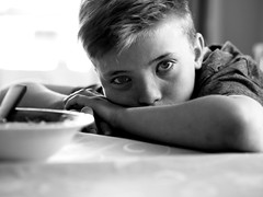 Mikael (livsillusjoner) Tags: boy boys kid kids child children young monochrome bw blackwhite blackandwhite contrast black white grey portrait people eat eating food table porridge glass drinking eyes