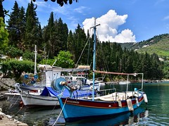 Fishing Boats (rustyruth1959) Tags: coast port water masts trees mountains fishingboats boats harbour kouloura corfu greece europe tamron16300mm nikond5600 nikon boat bay sky forest hull ropes clouds harbourside leaf leaves cypress moorings winch vessels canopy wheelhouse outdoor cuddy fenders village