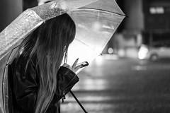 Message in the rain :-) (frank.gronau) Tags: umbrella regenschirm mobilephone handy frau mädchen woman girl white black weis schwarz licht light osaka nacht night regen rain raining street alpha sony gronau frank