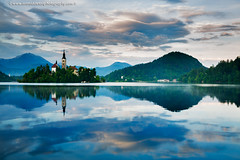 Sunset over Lake Bled (Ian Middleton: Photography) Tags: bled slovenia sunset alps lake church island tower bell history historic mountains backdrop karavank alpine building christianity christian tourists stunning scenic travel architecture architectural religious attraction slavic slovene former beautiful popular water european scenery eu eec europe vacation holiday touristy yugoslavia slovenian gorenjska famous reflection shimmering clouds evening tourist tourism trees clear still