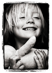 Joy (magnusmagnus) Tags: bear bw white black film girl smile photoshop d50 hair polaroid nikon teddy bears joy 85mm happiness memory frame nikkor colbert opinion permanent blissed stevencolbert oldglory stephencolbert faved f20 faveme abigfave faveme2 faveme3 faveme4 faveme5 faveme6 faveme7 scomp diamondclassphotographer